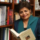 Photo of Vishakha Desai in front of book shelf and holding a book